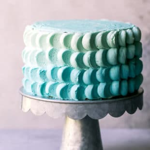 A metal cake stand with 6-inch funfetti cake, decorated with buttercream petals. Ombre smash cake for baby boy's first birthday.