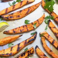 How To Grill Sweet Potato Fries on a servong platter, topped with chopped cilantro and lime juice.