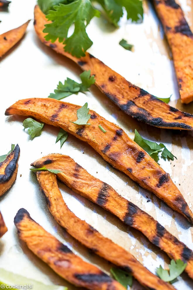 How To Grill Sweet Potato Fries - charred black grill marks, soft on the inside, sweet potato fries on a plate topped with cilantro.