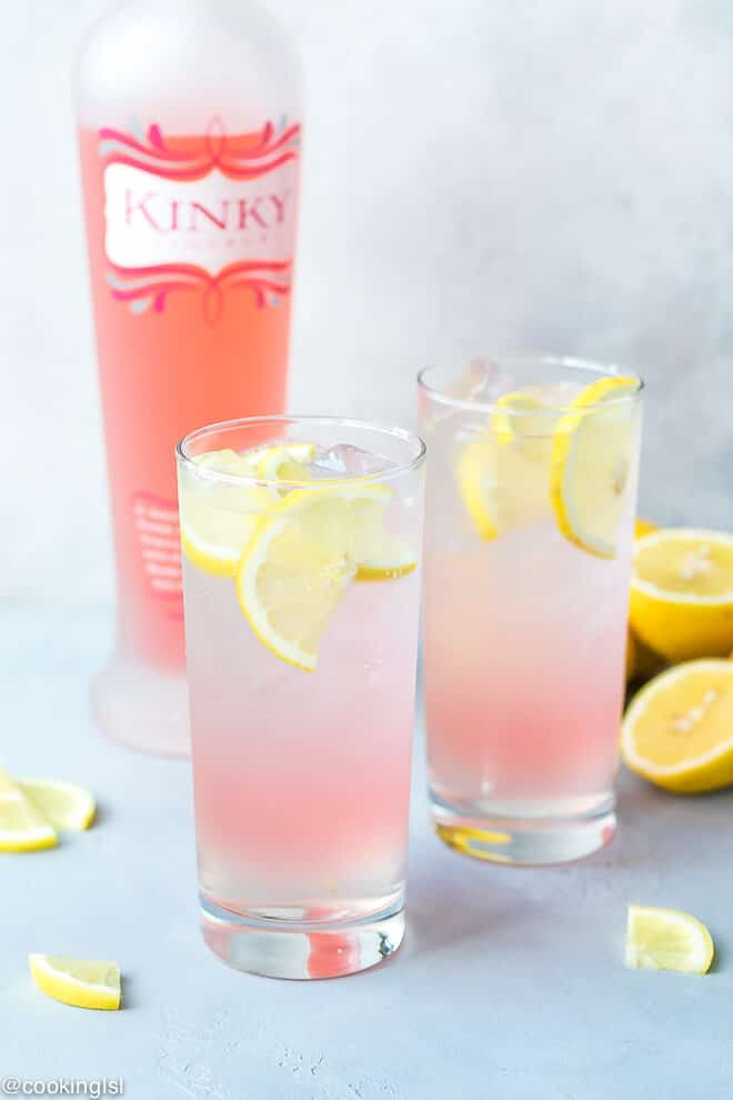 Tall clear glasses, filled with boozy lemonade cocktail. Pink Lemonade Vodka Cocktail- simple ingredient, perfect for a summer party, girly light pink color.