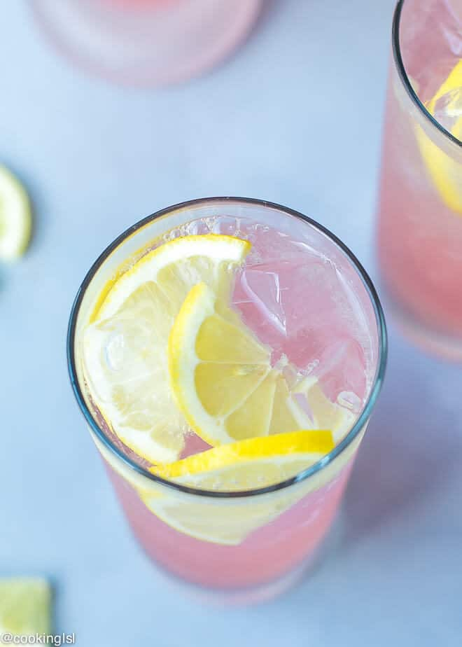 A glass full of pink lemonade vodka cocktail. Chilled, topped with lemon slices.