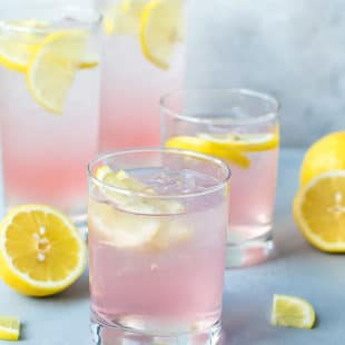 Glassed filled with pink vodka cocktail, perfect for summer parties. Pink Lemonade Vodka Cocktail Recipe-easy to make, made with KINKY Pink Liqueur. Glasses filled with ice , pink lemonade vodka and lemon slices.