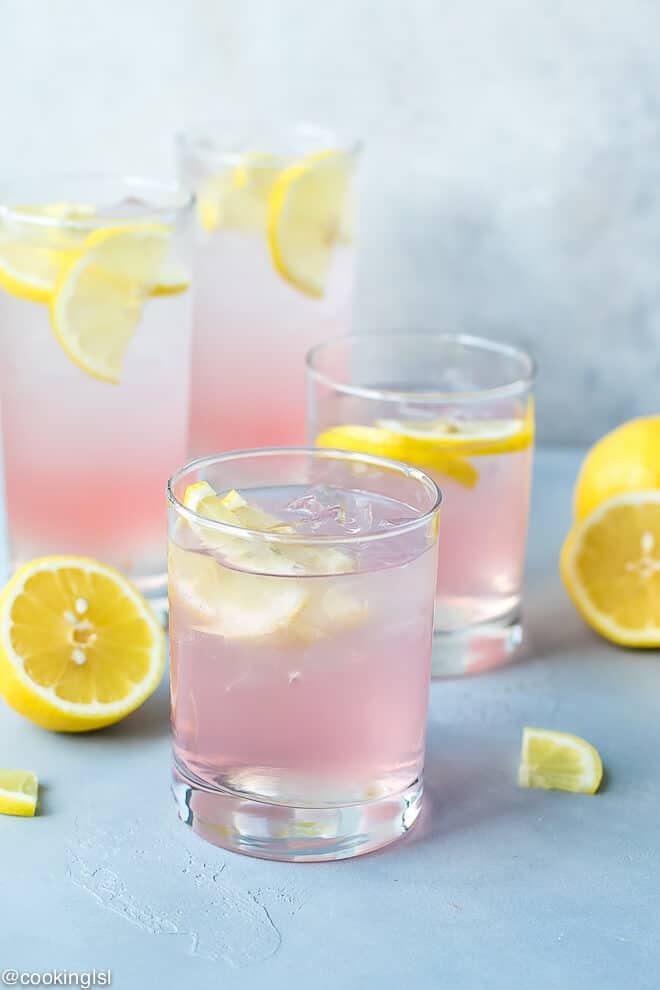 Glasses filled with pink vodka cocktail, perfect for summer parties. Pink Lemonade Vodka Cocktail Recipe-easy to make, made with KINKY Pink Liqueur. Glasses filled with ice , pink lemonade vodka and lemon slices.