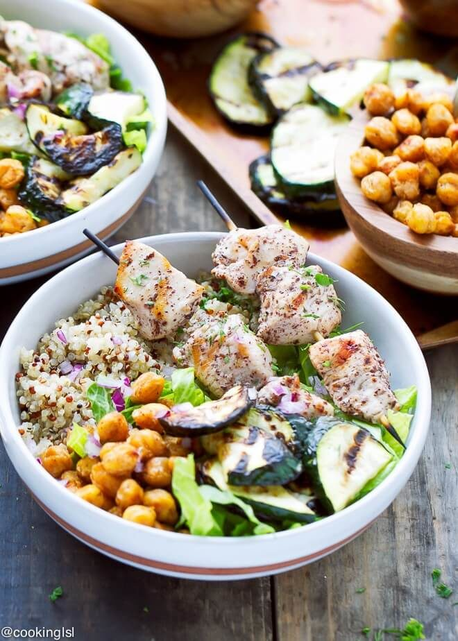 Sumac marinated pieces of chicken on wooden skewers, served over quinoa bowls with grilled zucchini, roasted chickpeas and lettuce.