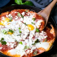 Simple ingredients and easy to make A plate with Potatoes With Tomato Sauce Feta And Eggs , runny egg yolk and delicious tomato sauce and potatoes combination. Eggs with potatoes and feta in a cast iron skillet. Cast iron skillet and wooden spoon.