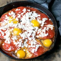 A plate with Potatoes With Tomato Sauce Feta And Eggs , runny egg yolk and delicious tomato sauce and potatoes combination. Eggs with potatoes and feta in a cast iron skillet.