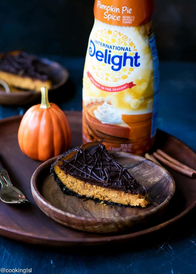 International Delight® Pumpkin Pie Spice Coffee Creamer used to make Dark Chocolate Pumpkin Pie With Chocolate Crust Recipe . Served on a wooden plate with decorative pumpkin next to it and wooden forks.