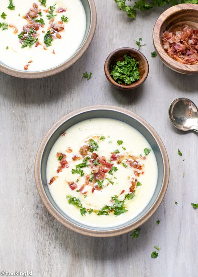 Bowls full of soup - Creamy Leek And Potato Soup With Bacon Recipe. Great for year round. Chopped parsley and bacon bits on the side. Olive oil swirl soup garnish.