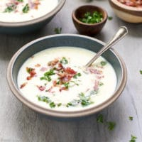 A creamic bowl full with warm and comforting Creamy Leek And Potato Soup With Bacon Recipe.