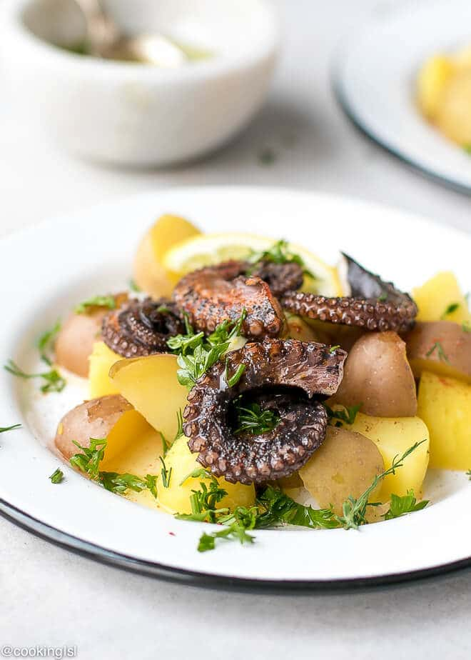A plate with warm octopus and potato salad. Grilled octopus with boiled potatoes recipe