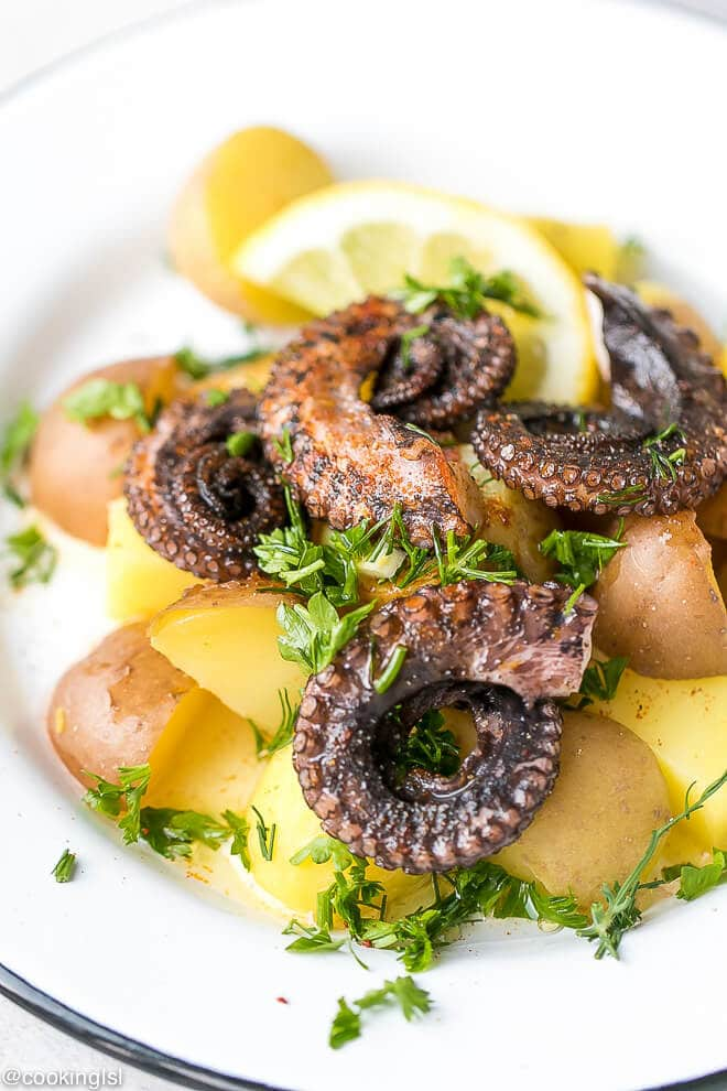 Tender, grilled octopus over boiled potatoes with paprika. Octopus and potato salad recipe.
