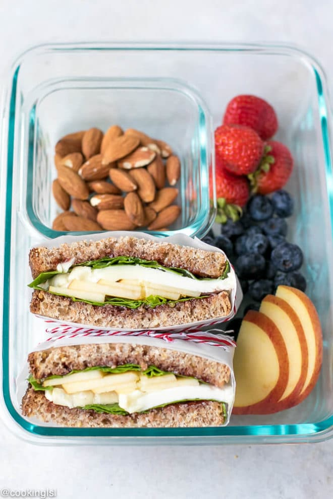 Apple Spinach Goat Cheese Sandwich - Packed Lunch. A Pyrex box with goat cheese sandwich packed to take to work. Nuts and fruit added for a healthy snack.