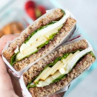Apple Spinach Goat Cheese Sandwich - Packed Lunch- two slices of whole grain bread with jam, spinach, apples and goat cheese in between. Cut in half for a healthy snack. Wrapped in parchment paper.