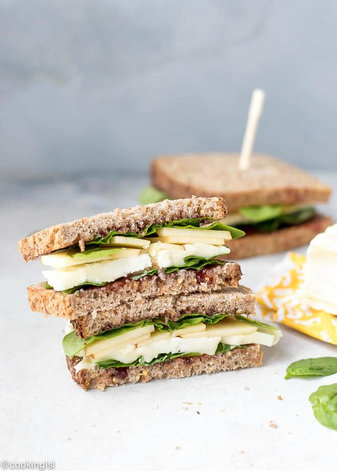 Apple Spinach Goat Cheese Sandwich - Packed Lunch. Two half sandwiches on top of each other. Slices of whole grain bread with spinach, jam, apple slices and creamy goat brie cheese. Great for lunch box.