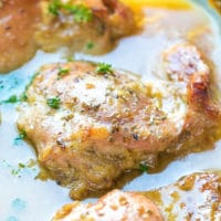 Crispy, juicy, delicious Easy Oven Baked Honey Mustard Chicken Thighs Recipe. In a baking dish with gravy from the sauce.