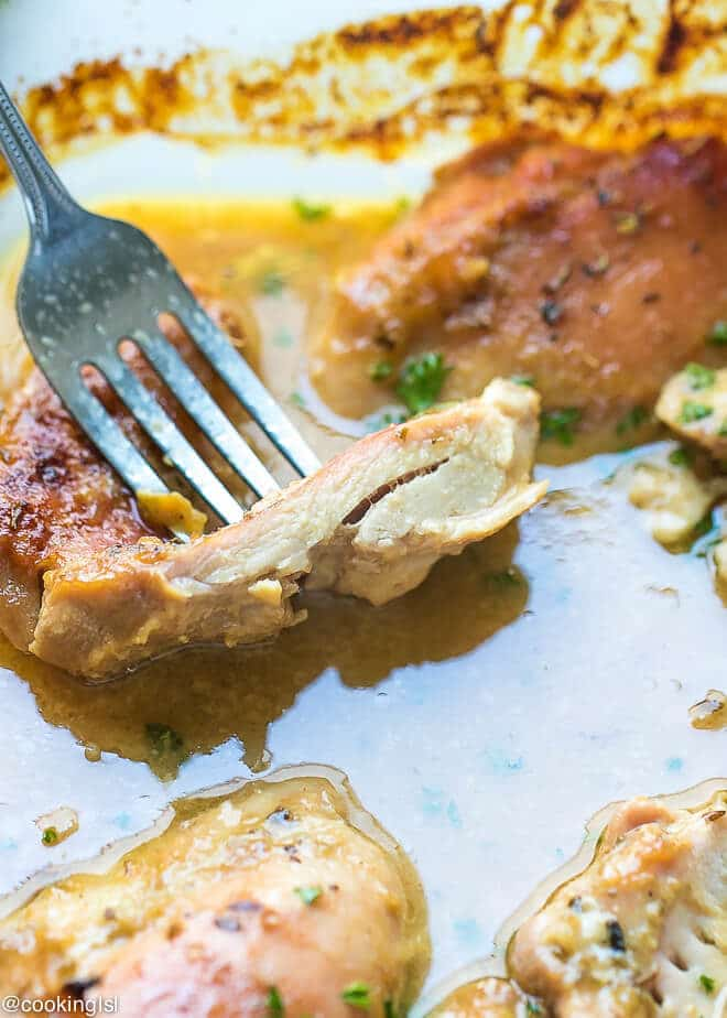Juicy quick and easy to make with a few ingredients, Easy Oven Baked Honey Mustard Chicken Thighs Recipe. Cut chicken thigjs, to show how juicy it is.