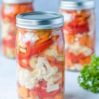 Ball Jars with easy canned vegetables cauliflower, carrots and red peppers recipe. Safe pickling method for crunchy garden vegetables.