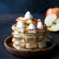 Caramel Apple Waffle Cake Recipe - waffle cake on a wooden plate with whipped cream , caramel and apples on top.