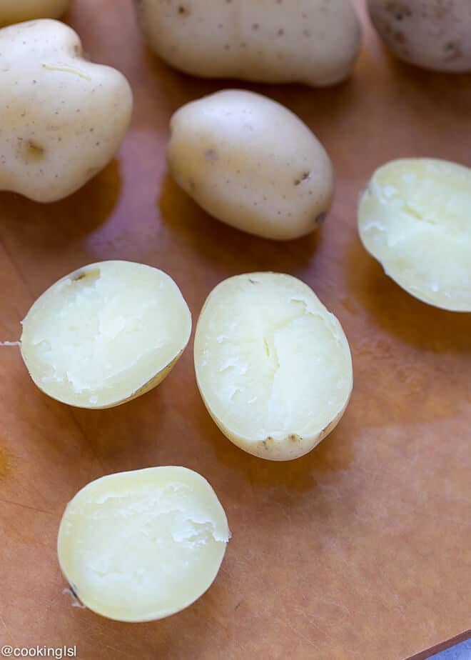 Cheesy Crispy Baked Potato Bites Recipe - boiled potatoes on a epicurean cutting board.