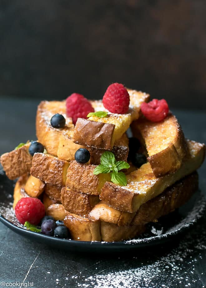 Baked French Toast Sticks Recipe - on a black plate topped with berries.