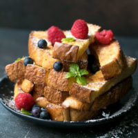 Baked French Toast Sticks Recipe on a plate, dusted with sugar and topped with berries.