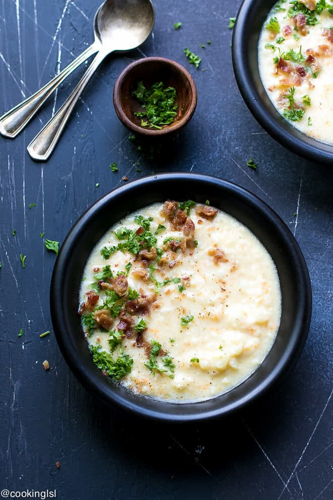 Cauliflower Cheese Soup Low Carb Recipe. Black ceramic bowl with cauliflower white cheddar soup and small wooden bowl with parsley. Spoons on the side.