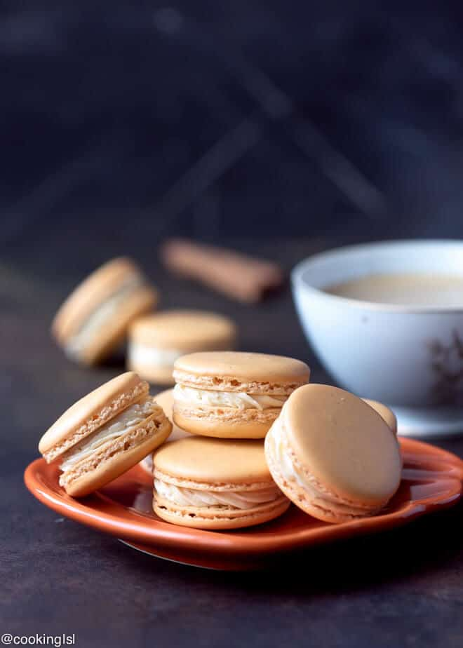 Pumpkin Spice Macarons Recipe. Orange pimpkin flavored macarons with Swiss meringue buttercream on an orange plate with a cup of coffee next to them.