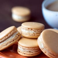 Pumpkin Spice Macarons Recipe on a fall orange plate with coffee on the side. Step by step instructions.