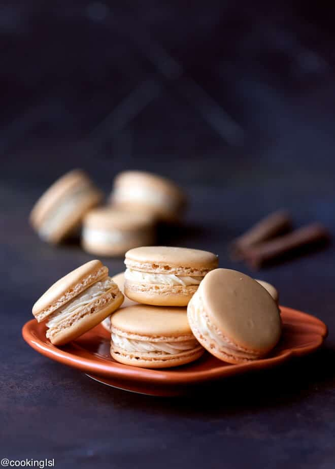 Pumpkin Spice Macarons Recipe With cinnamon sticks next to them.