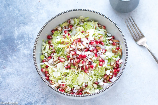 Shaved Brussel Sprouts Salad Recipe - bowl with green and colorful salad and a dressing container next to it. White balsamic vinegar dressing.