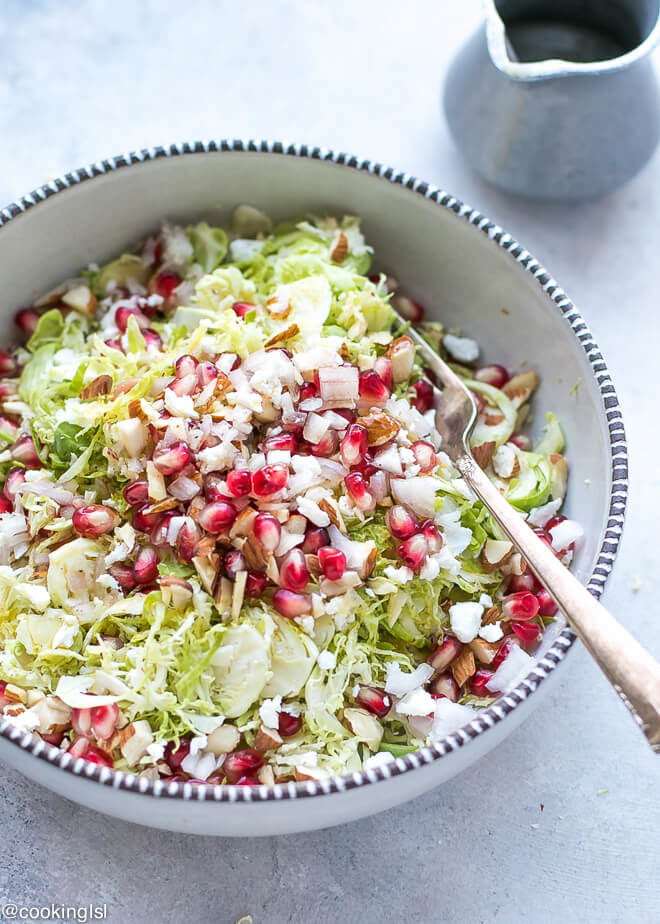 A ceramic pottery bowl with shaved Brussel sprouts salad with almonds, pomegranate and feta,