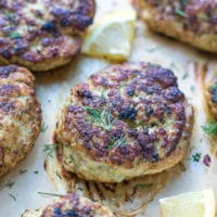Oven Baked Turkey Zucchini Burgers Recipe. Turkey zucchini patties on parchment paper, topped with dill.