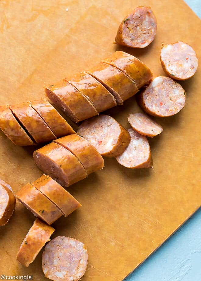 A cutting board with andouile sausage.