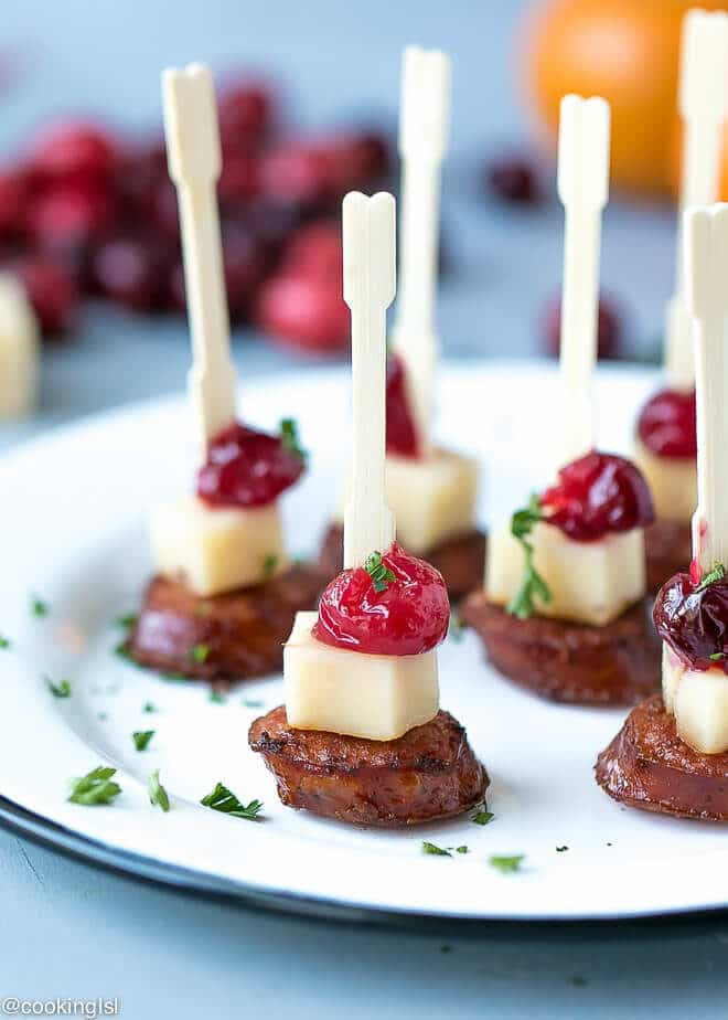 Andouille Sausage Appetizer Bites With Cranberry Cheddar. On a white platter, made with wooden skewers, toothpick, festive, party food.