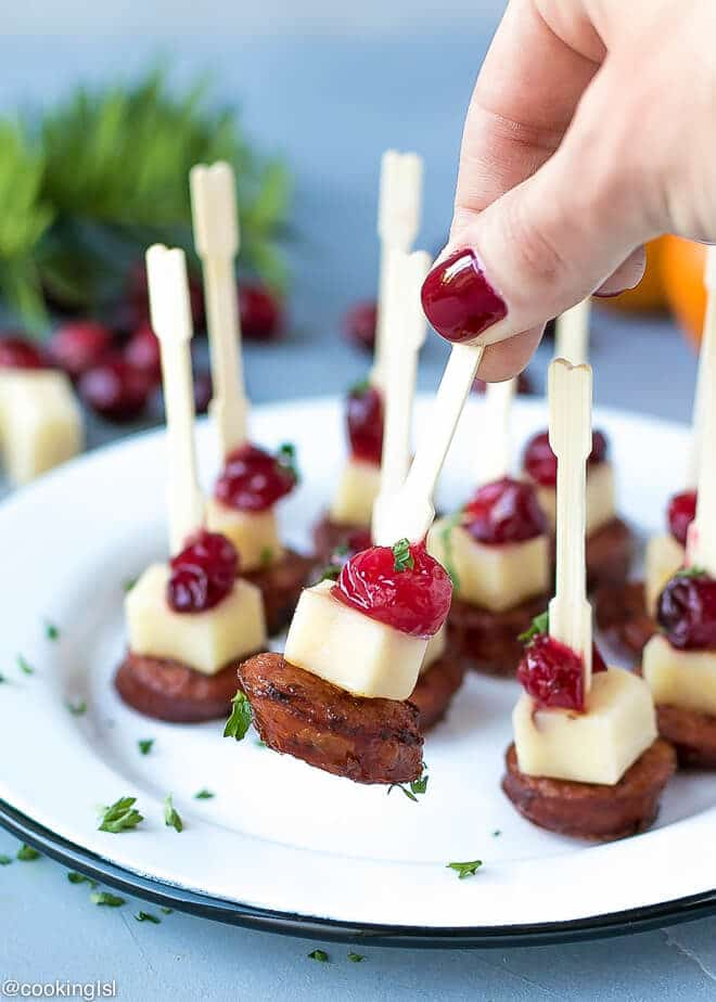 Andouille Sausage Appetizer Bites With Cranberry Cheddar - mini bites on a plate with wooden skewers, held in hand.