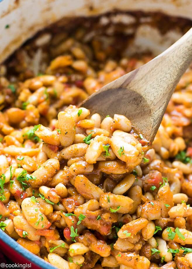 Easy Bulgarian Baked Beans Recipe in a large pot with a wooden spoon inside. Garnished with parsley.