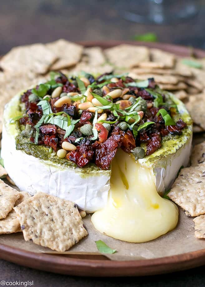 Baked savory brie appetizer, runny, oozy, gooey cheese, topped with sun dried tomatoes, bacon, basil and pine nuts