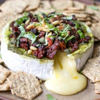 Savory Baked Brie Appetizer Recipe. Brie wound on a platter, topped with pesto, sun dried tomatoes, pine nuts, basil and crackers next to it.