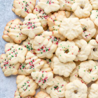 Easy Cream Cheese Spritz Cookies Recipe on a platter, in the shape of Christmas Trees and Wreaths, topped with sprinkles.