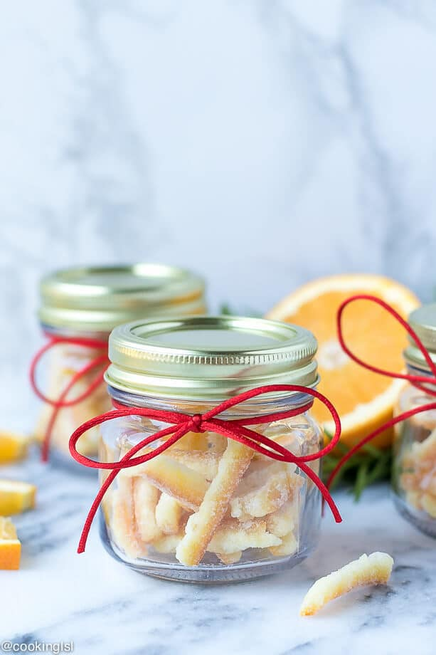 Small gift jars filled with candied orange peel slices, rolled into sugar. Easy candied orange peel recipe.