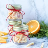 Small cute clear jars with red ribbon bows, filled with candied orange peel. Easy candied orange peel recipe. Sliced orange on the side.