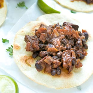 Barbacoa Tostadas Recipe With Frontera Frozen Skillets , barbacoa, sauce and beand on top of crispy flour tortilla.