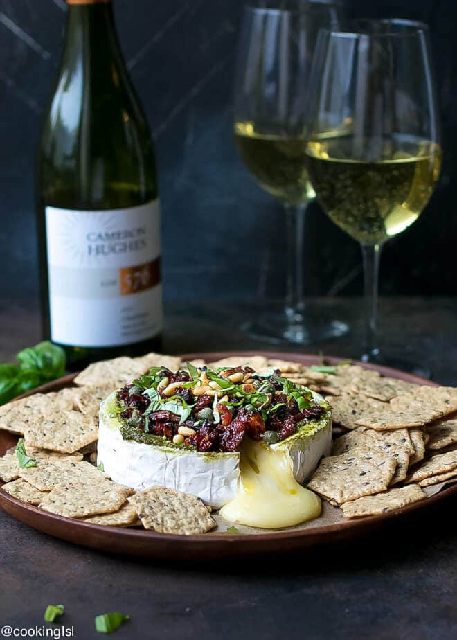 Savory Baked Brie Appetizer Recipe. A round of Brie on a wooden platter, topped with pesto, sun dried tomatoes, basil, pine nuts and served with healthy crackers.Bottle of Cameron Hughes Chardonnay wine with two glasses next to it.
