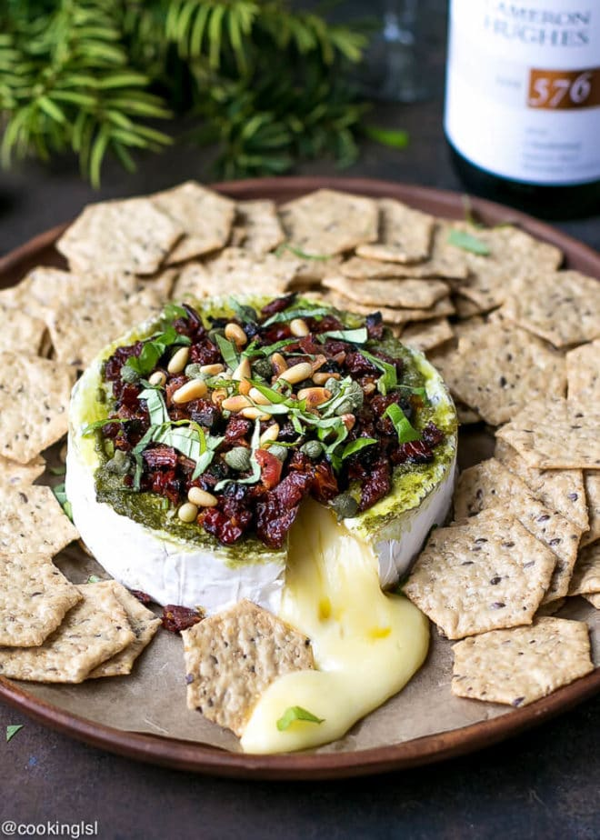 Savory Baked Brie Appetizer Recipe. A round of brie on a wooden platter in winter holiday setting, with a bottle of white wine next to it.