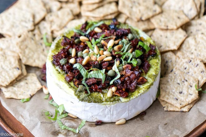 Savory Baked Brie Appetizer Recipe. A round of brie on a wooden platter in winter holiday setting with crunchy crackers around it.