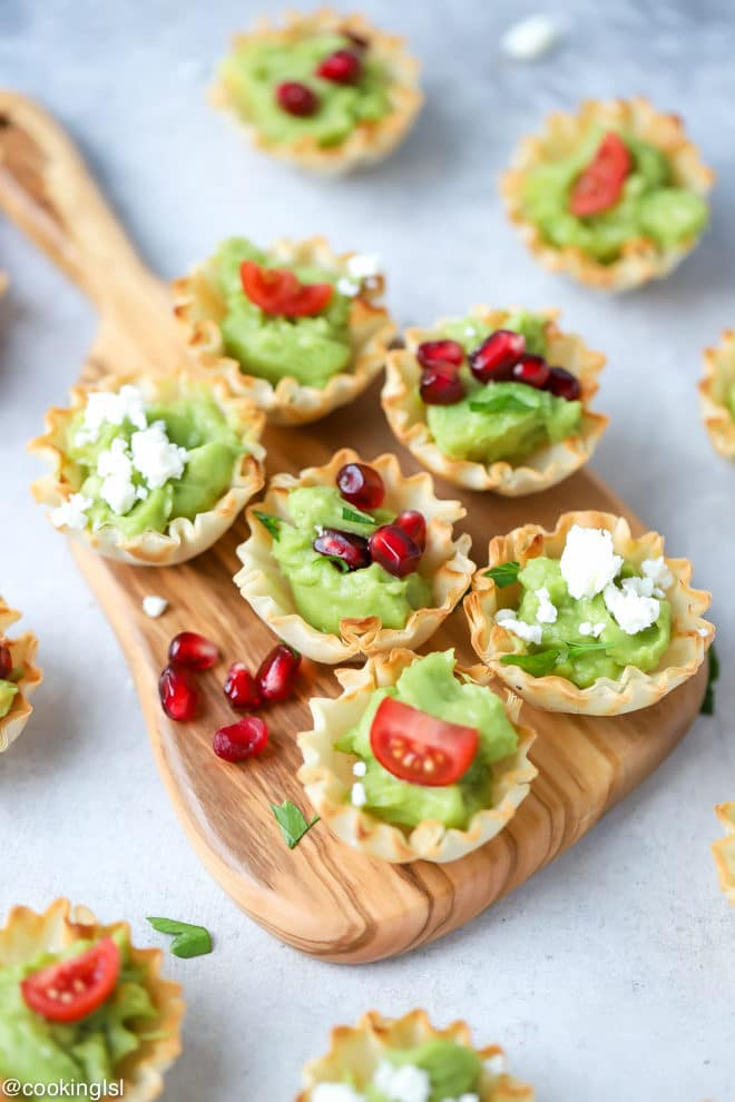 Avocado Filo Cups - Simply Avocado Wholly Guacamole dips, filo shells filled with avocado on a cutting board.