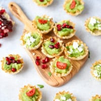 Avocado Filo Cups - Made with Simply Avocado Sea Salt And Garlic Herb Dips. Mini filo cups filled with avocado, on a wooden mini cutting board.