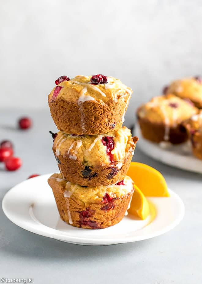 Healthy Cranberry Orange Muffins Recipe Refined Sugar Free stacked on top of each other with orange slices on the side.