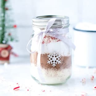 A 16 oz Ball Jar with Hot Cocoa Mix In A Jar, decorated With Christmas ribbon (bow) and stickers, Optional free printable.