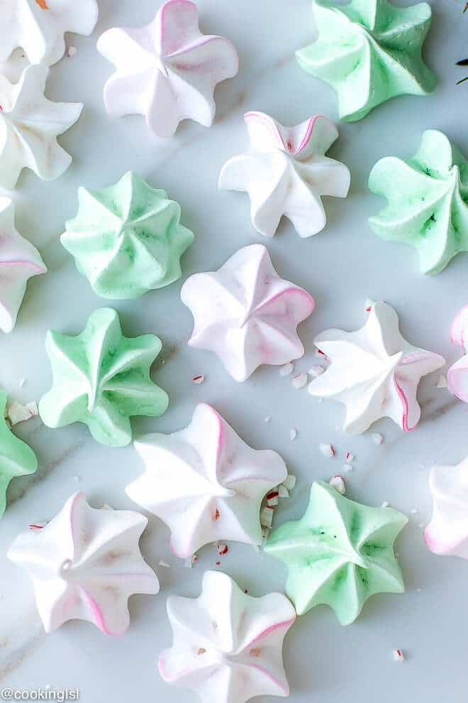 Mini Meringue Cookies Recipe on white marble platter, colored in light green and red.